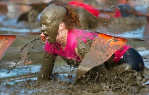 A competitor crawls through mud during t